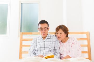 本を読むシニア夫婦 ベッド