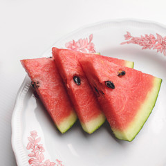 Watermelon is a piece Placed on a white saucer.