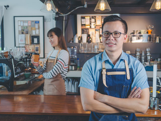 Asian man barista wear blue apron successful small business owner standing with employee in background preparing coffee at bar counter, Owner small business concept.