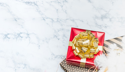 Top view of red glossy present box with golden bow and ribbon lay under white christmas tree on white marble floor,Holiday gift giving banner,leave space for adding text.
