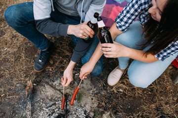 Hungry couple roasts sausages bonfire drink beer concept. Tourism romance. Camping lifestyle.