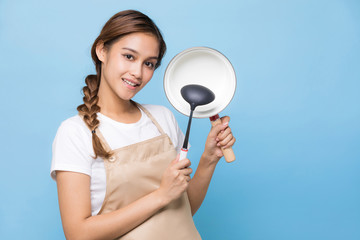 Young woman holding a pot and a ladle.