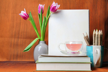 A study with books, vase of Tulips,a tea cup and a pencil stand with pencils.