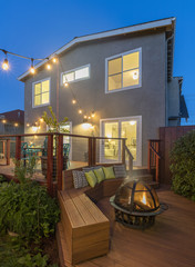 Home with furniture patio/ fire pit / wooden deck at twilight