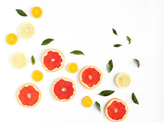 Pattern of fresh fruits on a white background, top view, flat lay.   Composition of green leaves and slices of citrus fruits: grapefruit, lemon, mandarin. Healthy food background, wallpaper, collage.