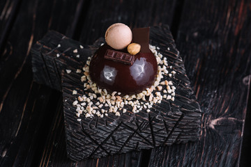 French chocolate mousse cake on wood background. Dessert decorated with macaroon, nut and piece of chocolate bar