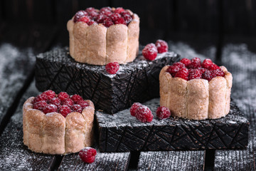 Three charlotte cakes with raspberry on wood background Wall mural