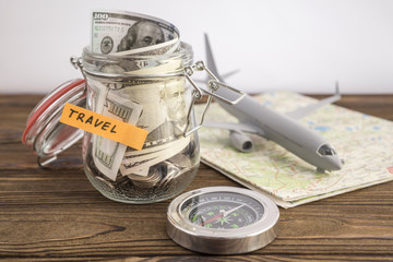 Budget Travel concept. Travel money savings in a glass jar with toy aircraft on world map and compass. to save for the trip
