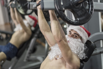 Young fitness santa training in gym lifting weights in christmas crossfit session