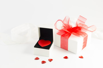 A red velvet heart in a white jewelry box, a white gift box with red ribbon and small shiny red decorative hearts on white background.