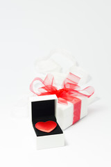 A red velvet heart in a white jewelry box and a white gift box with red ribbon on white background.