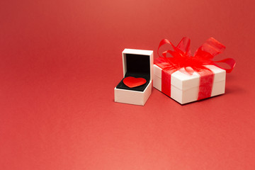 A red velvet heart in a white jewelry box and a white gift box with red ribbon on red background.
