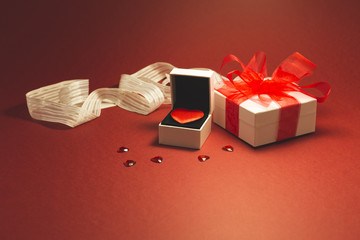 A red velvet heart in a white jewelry box, a white gift box with red ribbon and small shiny red decorative hearts on red background.