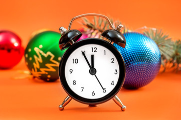Clock with christmas toys and branch of fir tree on bright orange background. New year background.