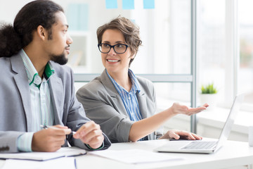 Confident businesswoman pointing at laptop display during presentation of her ideas to colleague