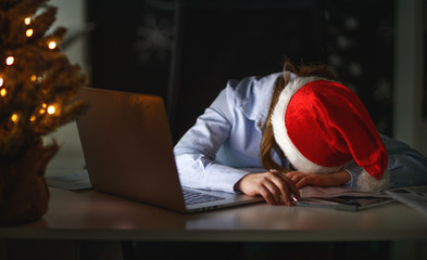 businesswoman freelancer tired, asleep working at computer at Christmas
