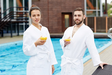 Young restful couple in white bathrobes holding glasses of juice while standing by swimming-pool