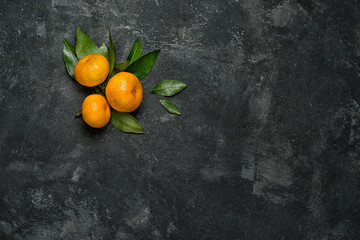 group of three mandarines with leaves on a black cement background with copy space for your text