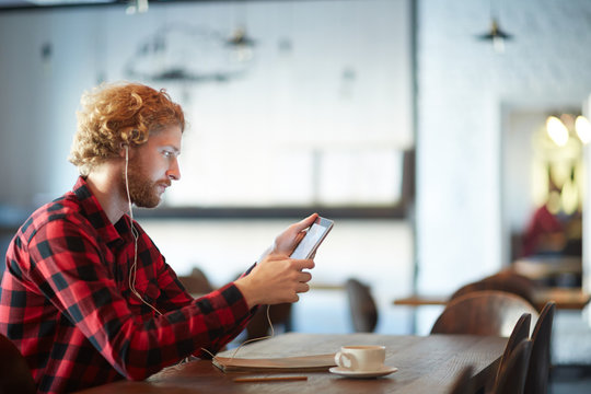 Guy with tablet listening to online lectures in earphones while sitting in cafe