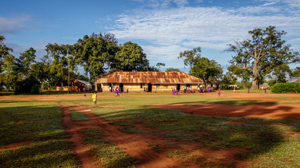 KOLONYI, UGANDA – NOVEMBER 09, 2017: Many students with purple uniform waiting to enter the primary school in Kolonyi near Mbale in Uganda on a beautiful morning in November