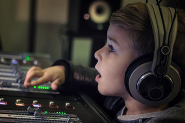 Close up of boy with headphones at audio mixing desk.