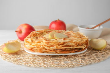 Plate with delicious thin pancakes and sliced apple on table