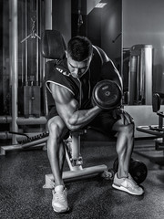 Muscular bodybuilder sitting on a bench in the gym coaches the biceps lifting the dumbbell. Black and white photography.