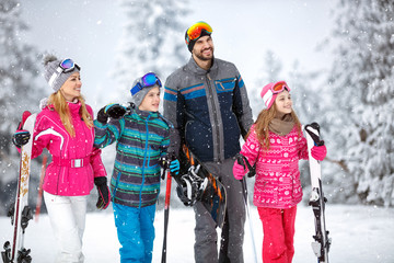 Family on winter holiday going to ski terrain