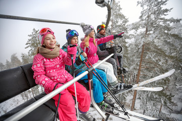 Happy family lifting on ski terrain