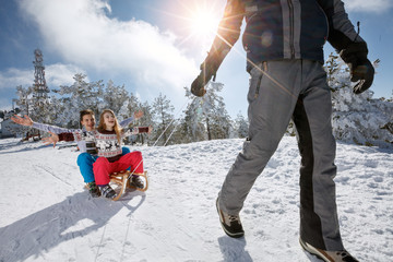 Boy and girl sitting on sleds and father pulling them