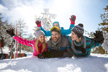 Cheerful parents with children on snow