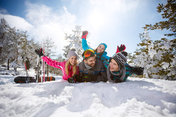Young family having fun on snow in mountain