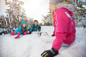 Mother with children on skiing resting on snow