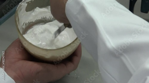 Close-up of a dental technician who is mixing plaster in a