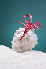Christmas toy - a white glass cone lies on the snow