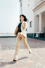 a beautiful girl with a dark long straight hair in a beige strict suit is in a motion near an amazing architecture