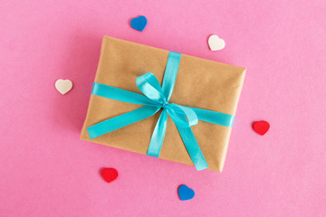 Gift box wrapped of craft paper and blue ribbon with colorful hearts on the pink background, top view.