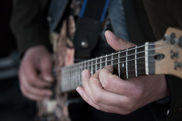 Hands of the musician playing the guitar. Fretboard, fingers, strings