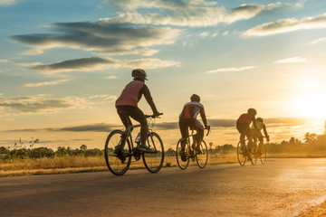 Group of  men ride  bicycles at sunset with sunbeam over silhouette trees background. Wall mural