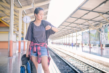 Portrait of young beautiful asian woman looking at her watch while waiting for the train at the railway station. Woman travel backpack checking the time on her watch. Holiday tourist concept.