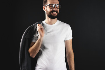 Smiling handsome hipster with coat on shoulder wearing white blank t-shirt on dark background. Bearded man in glasses and empty tshirt