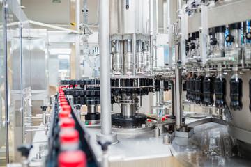 Bottling factory - Black juice bottling line for processing and bottling juice into bottles. Selective focus.