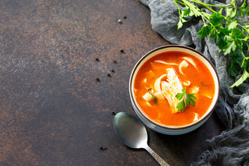 Tomato soup with pasta and chicken in a bowl on a dark stone background. The concept of healthy eating. Copy space.