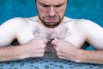 Caucasian dude swimming in pool. he is looking on his hair on chest