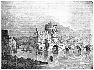 Medieval stone bridge leading to an ancient fortress on a lake in a rocky land, Euripus bridge Greece. Old Illustration by unidentified author published on Magasin Pittoresque Paris 1834