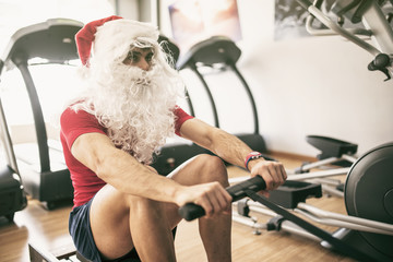 Santa claus training in rowing machine after christmas holidays reducing his fat percentage