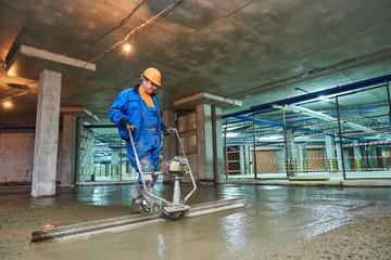 concrete floor construction. Worker with screeder