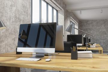 Black computer screen in a concrete office