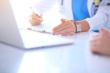 Doctor and patient couple are discussing something,sitting on the desk