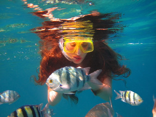 girl among tropical fish in Red Sea, Eilat, Israel